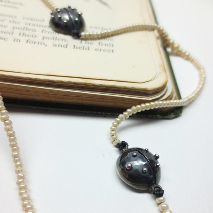 Oxidised Ladybirds threaded onto glass beads.